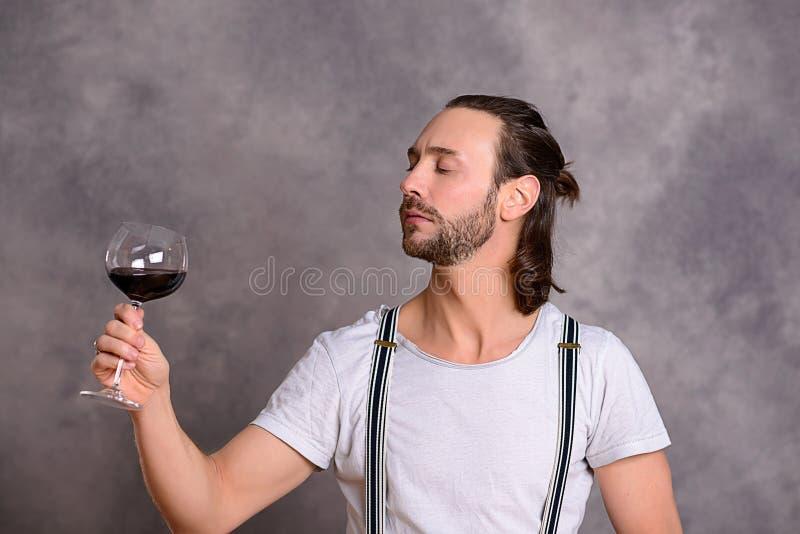 Dricka rött vin för ung man royaltyfria foton