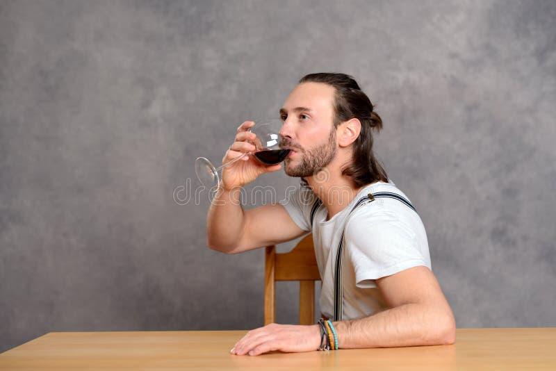 Dricka rött vin för ung man royaltyfri foto