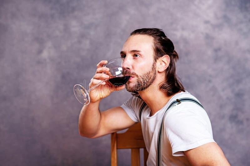 Dricka rött vin för ung man fotografering för bildbyråer