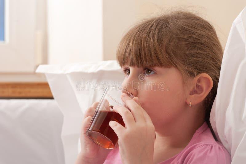 Dricka tea för flicka, medan sitta i underlag. Närbild. arkivbilder