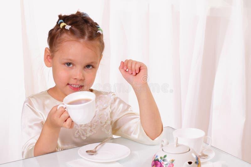 Dricka tea för nätt liten flicka royaltyfria foton