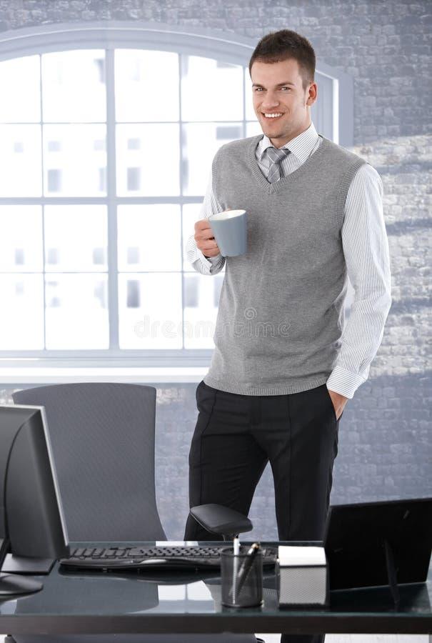 Dricka tea för tillfällig affärsman i regeringsställning som ler arkivfoto
