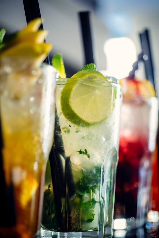 Dricka timmar Saftiga drycker med alkohol på räknare Coctailar tjänade som i exponeringsglas med dricka sugrör iced drinkar arkivbild