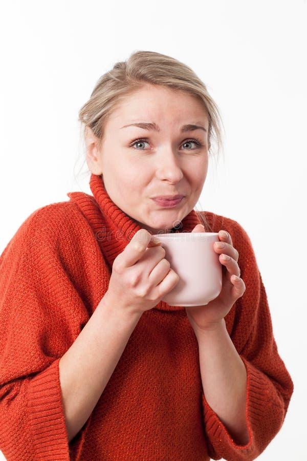 Dricka varma drycker för den lyckliga blonda flickan som rymmer ett varmt te royaltyfri bild