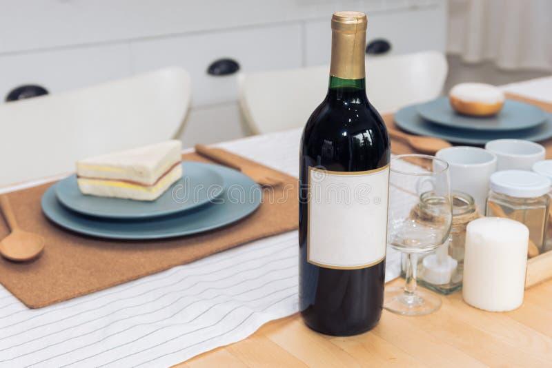 Dricka vinflaskan på den äta middag tabellen Dryck- och matbegrepp arkivfoton