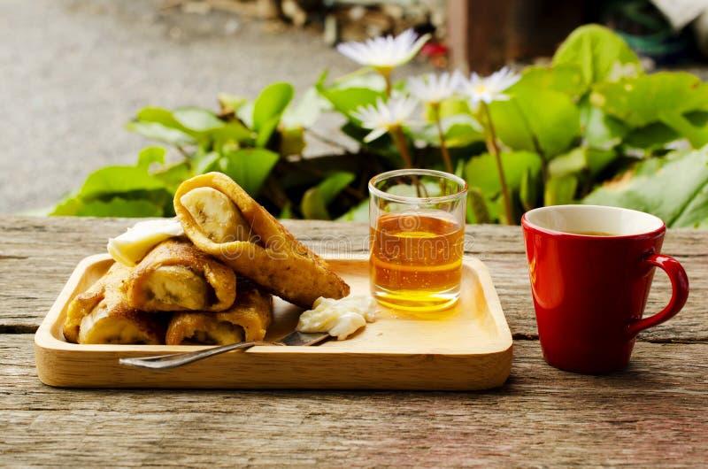 Dricker franskt rostat bröd för bananen med honung och varmt kaffe på röda koppar royaltyfria foton