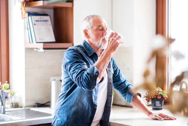 Dricksvatten för hög man i köket royaltyfri bild
