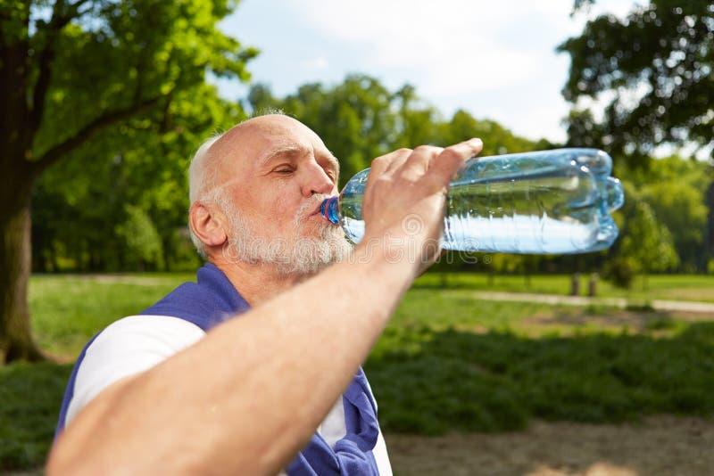 Dricksvatten för hög man, når att ha gjort sportar fotografering för bildbyråer