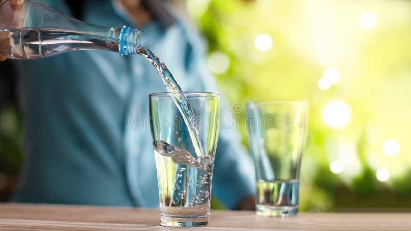 Dricksvatten för hand för kvinna` s hällande från flaskan in i exponeringsglas arkivfoto