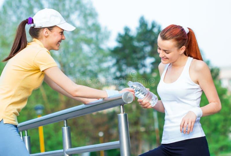 Dricksvatten för två lyckligt konditionkvinnor fotografering för bildbyråer