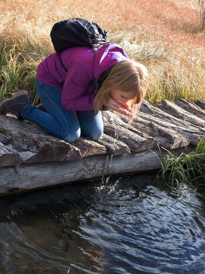 Dricksvatten för ung kvinna från utomhus- ström med henne händer royaltyfri fotografi