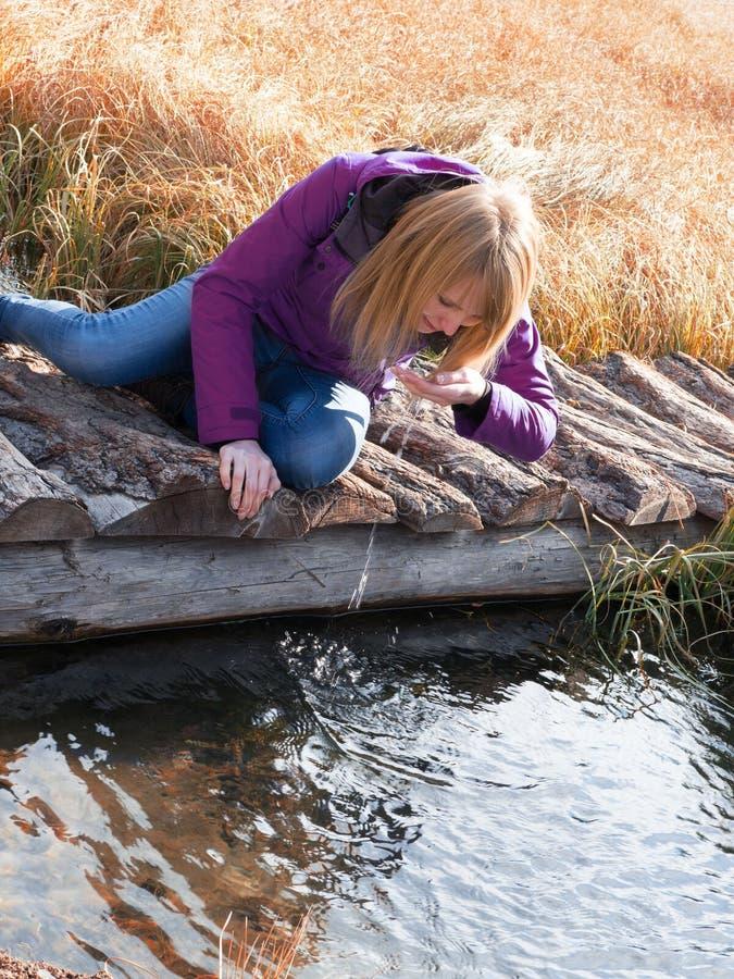 Dricksvatten för ung kvinna från utomhus- ström med henne händer royaltyfri bild