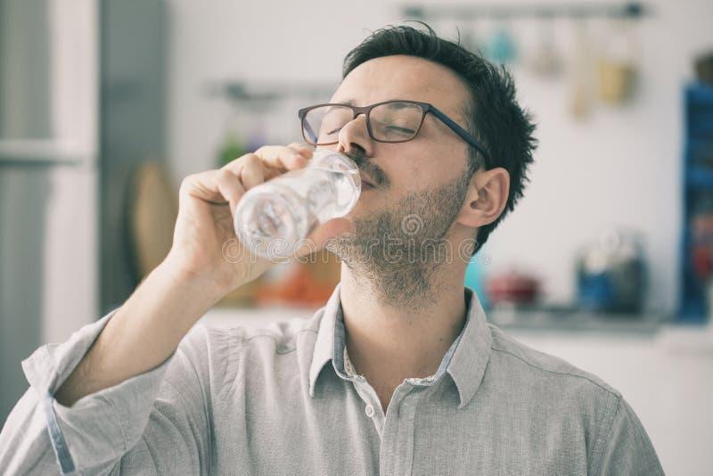 Dricksvatten för ung man från flaskan i kök arkivbild