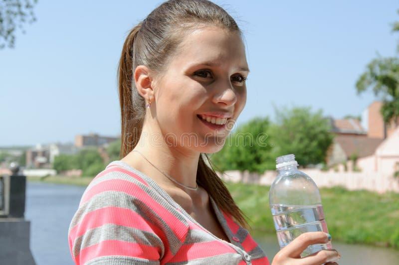 Dricksvatten och le för sportkvinna arkivfoton