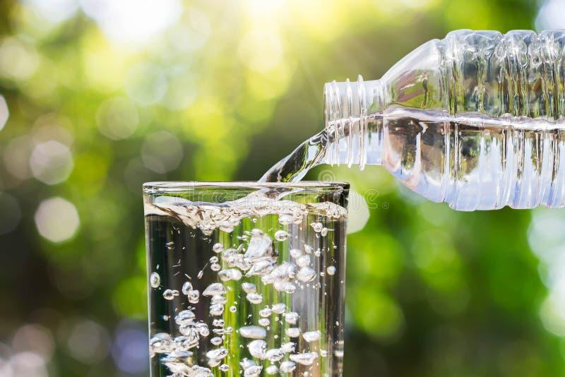 Dricksvatten som häller från flaskan in i exponeringsglas på suddig ny grön naturbokehbakgrund arkivfoto