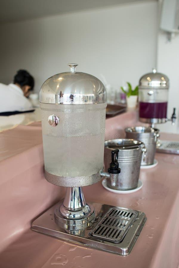 Dricksvattenbehållare Dricka behållarebehållaren med kallt vatten i restaurang Kallt vatten och is på en tabell arkivbild