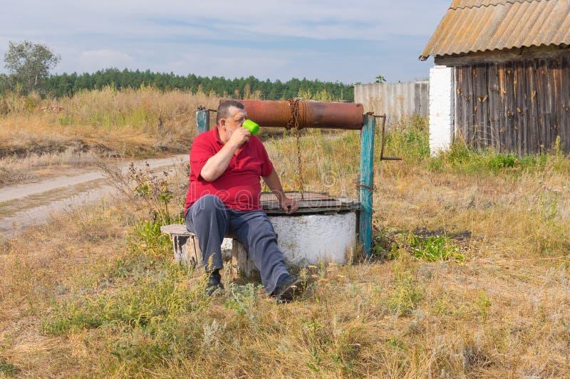 Dricksvattensammanträde för hög man på en bänk nära en gammal attraktion-brunn royaltyfri bild