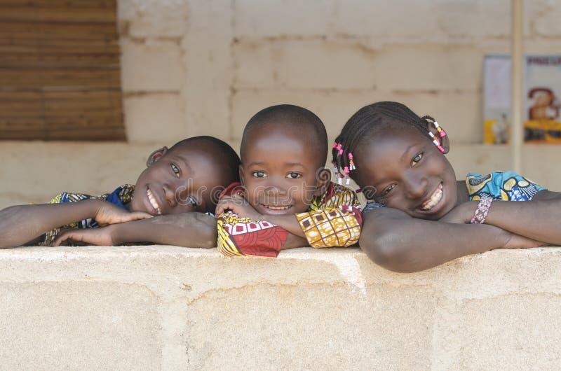 Drie Aanbiddelijke Afrikaanse Kinderen die in openlucht Exemplaarruimte stellen stock foto's