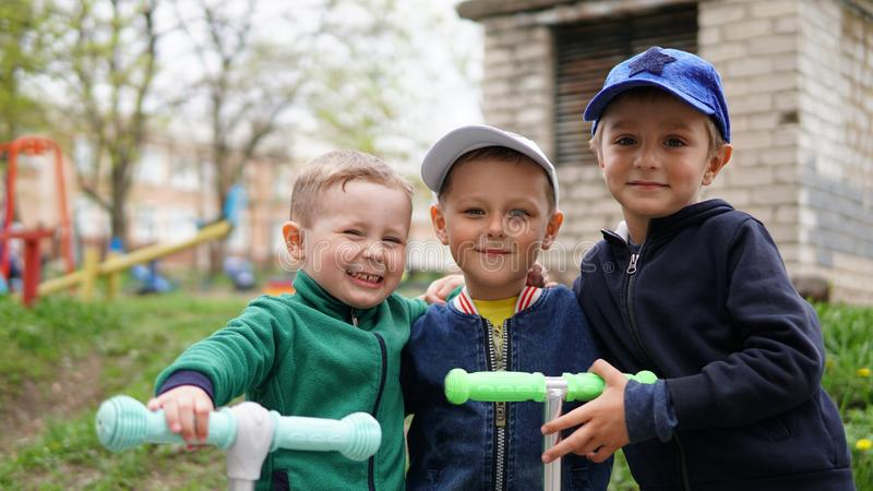 Drie aanbiddelijke kleine kinderen die op schopautopedden bij speelplaats berijden royalty-vrije stock afbeeldingen