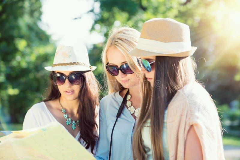 Drie aantrekkelijke meisjes die richtingen op een kaart zoeken bij de zomervakantie royalty-vrije stock afbeelding
