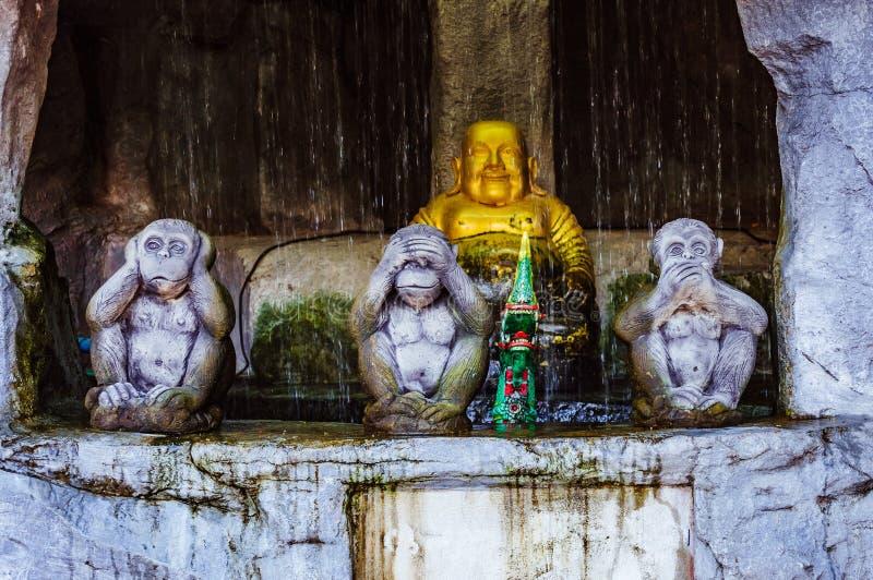 Drie aapstandbeelden met Boedha op de achtergrond royalty-vrije stock foto's