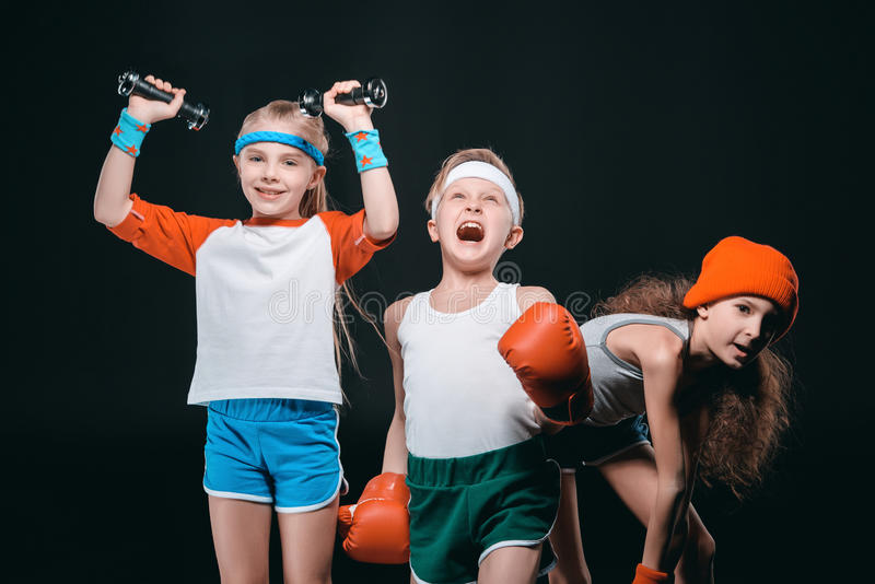 Drie actieve jonge geitjes in sportkleding het stellen met sportmateriaal royalty-vrije stock foto