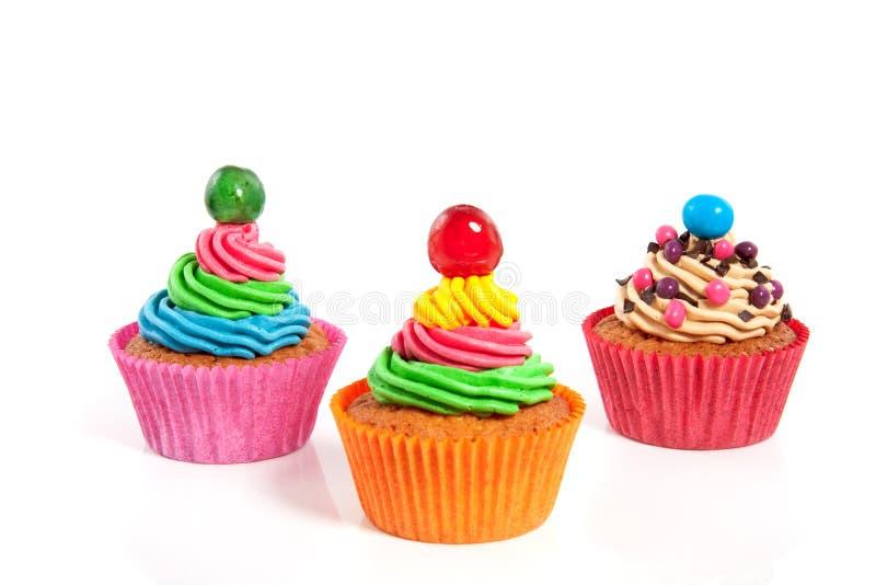 Drie afgeroomd kleurrijk cupcakes stock foto