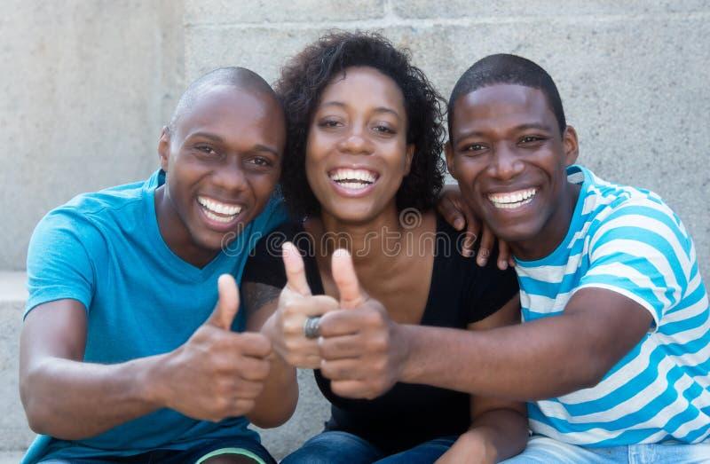 Drie Afrikaanse Amerikaanse mannen en vrouw die duim tonen stock afbeeldingen