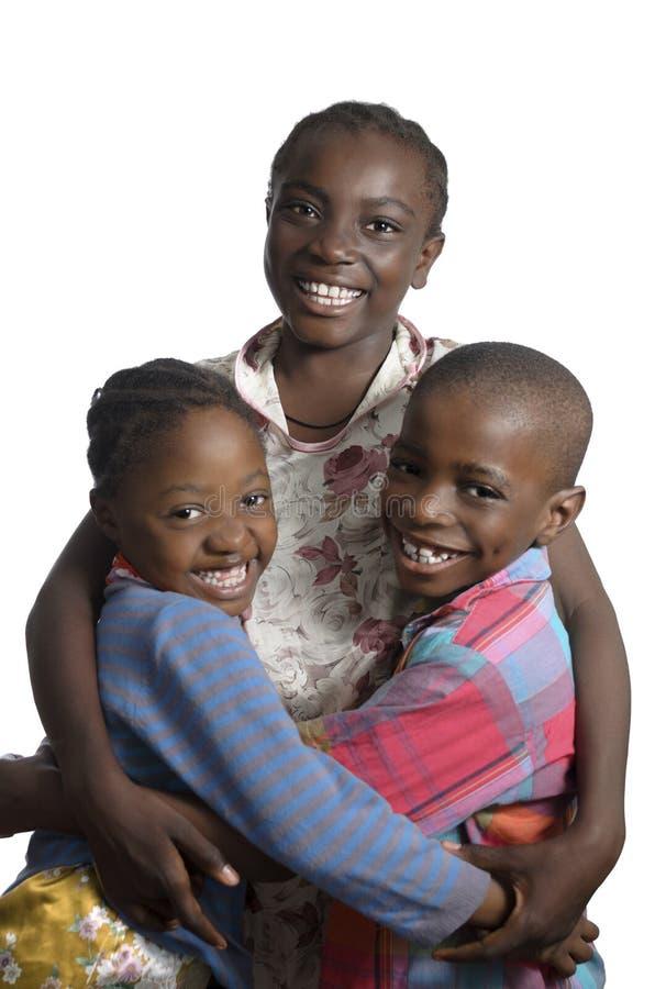 Drie Afrikaanse jonge geitjes die bij een andere het glimlachen houden stock foto's