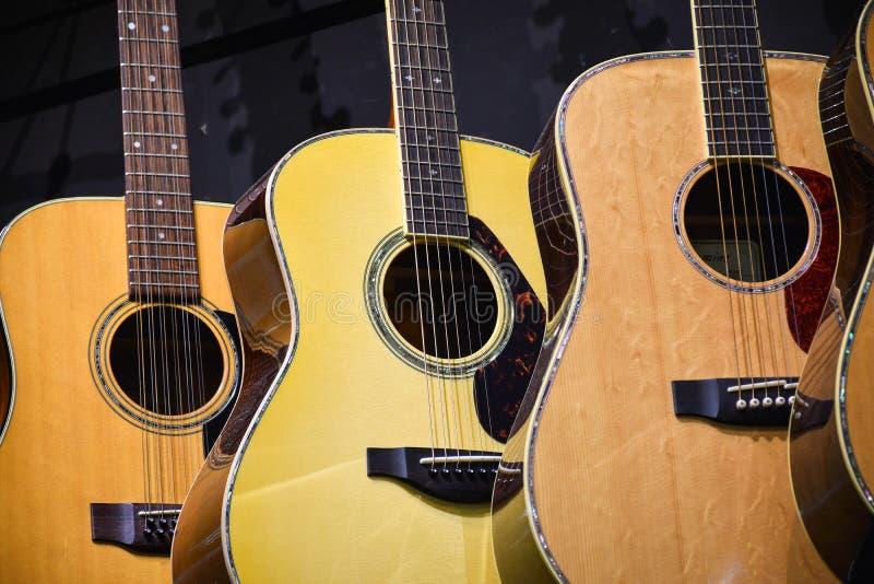 Drie akoestische gitaren die generisch op een rij - hangen stock foto