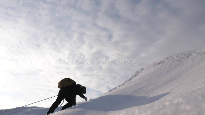 drie Alpenists in de winter beklimmen kabel op berg De reizigers beklimmen kabel aan hun overwinning door sneeuwhelling in sterk royalty-vrije stock fotografie