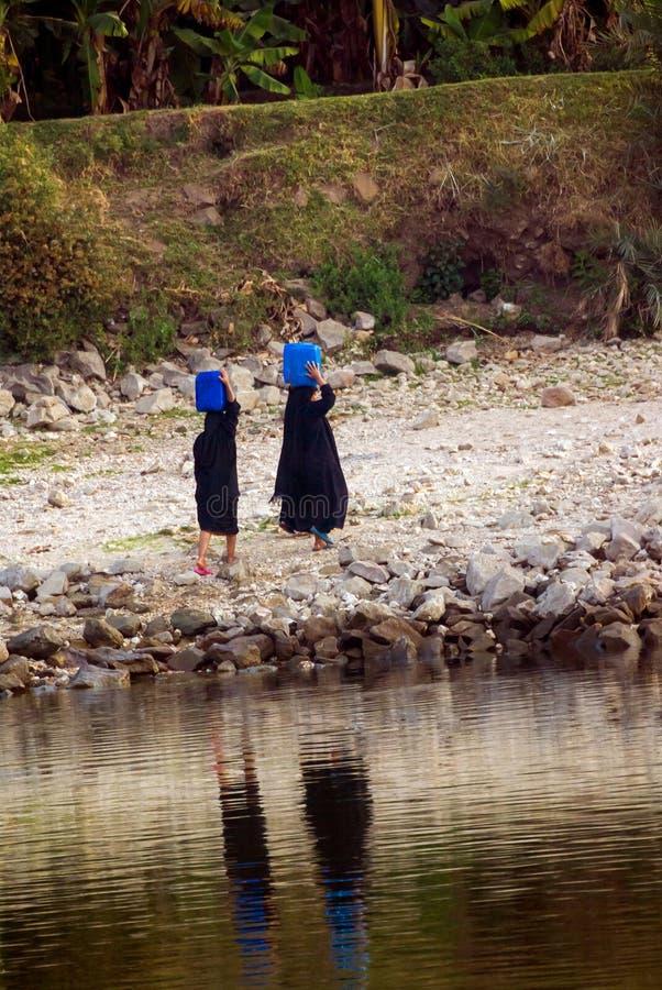 Drie Arabische vrouwen kleedden zich volledig in zwarte dragende jerrycans op hun die hoofden met water van Nile River in Egypte, stock foto's