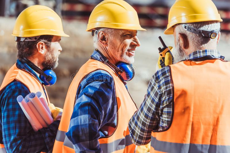 Drie arbeiders in bouwvakkers en weerspiegelende vesten die zich bij bouwwerf en het spreken bevinden stock afbeeldingen