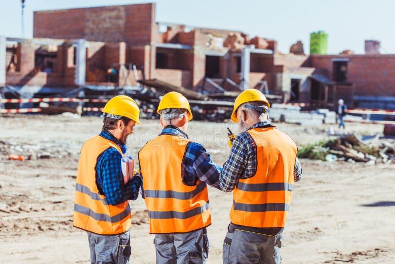Drie arbeiders in bouwvakkers en weerspiegelende vesten status stock afbeeldingen