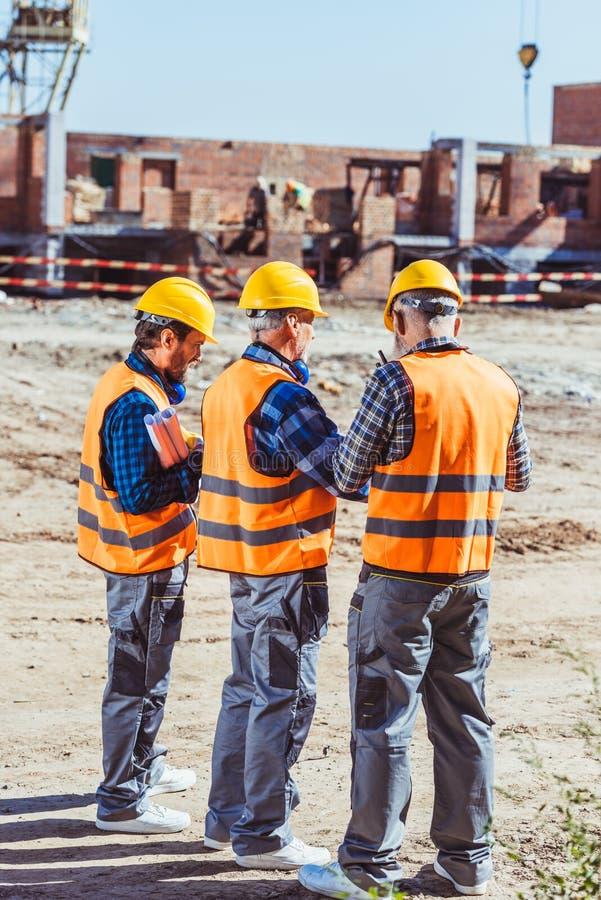 Drie arbeiders in bouwvakkers en weerspiegelende vesten status royalty-vrije stock afbeelding