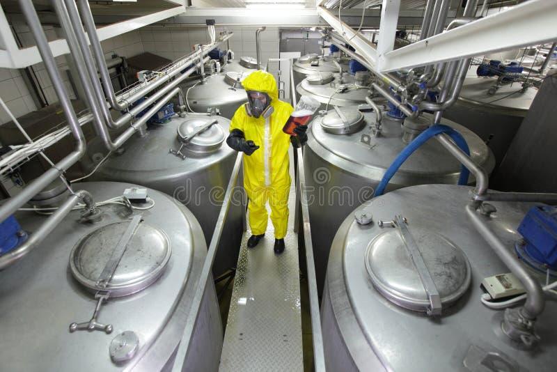 Drie arbeiders die bij grote zilveren tanks in installatie werken stock afbeelding