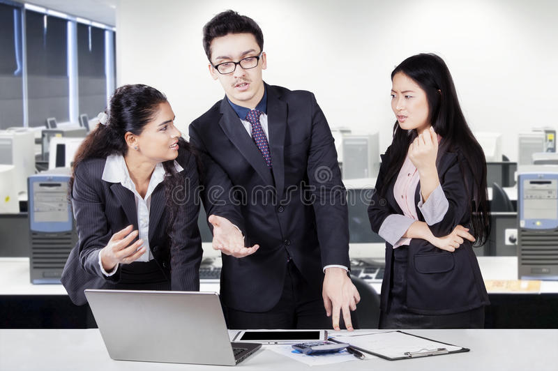 Drie arbeiders die in het bureau debatteren stock foto