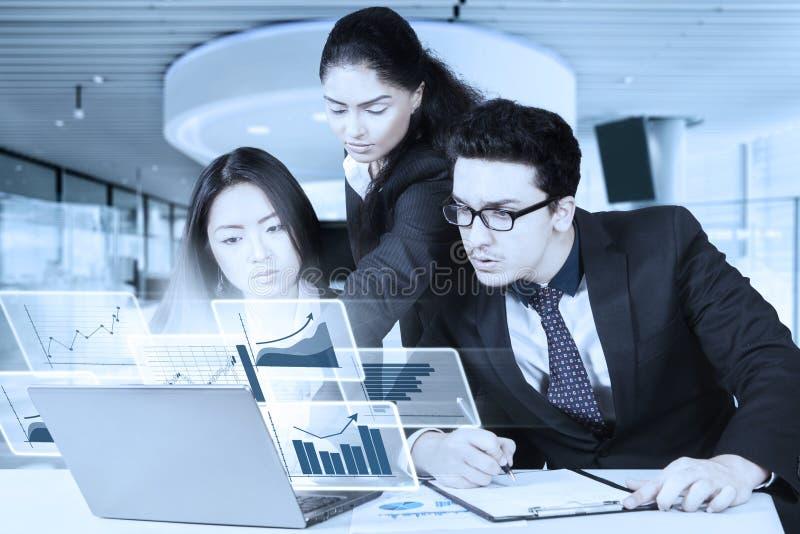 Drie arbeiders met virtuele grafiek stock foto