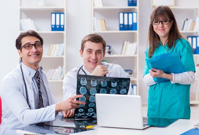 Drie artsen die aftastenresultaten van x-ray beeld bespreken stock foto