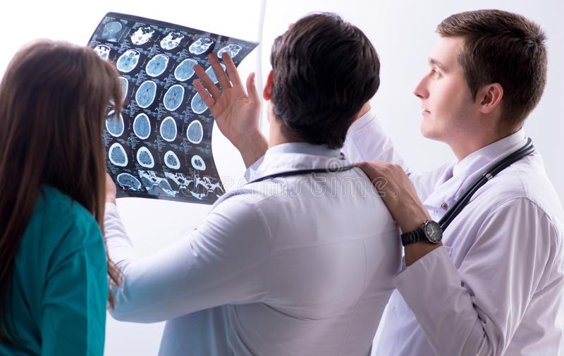 Drie artsen die aftastenresultaten van x-ray beeld bespreken stock afbeeldingen