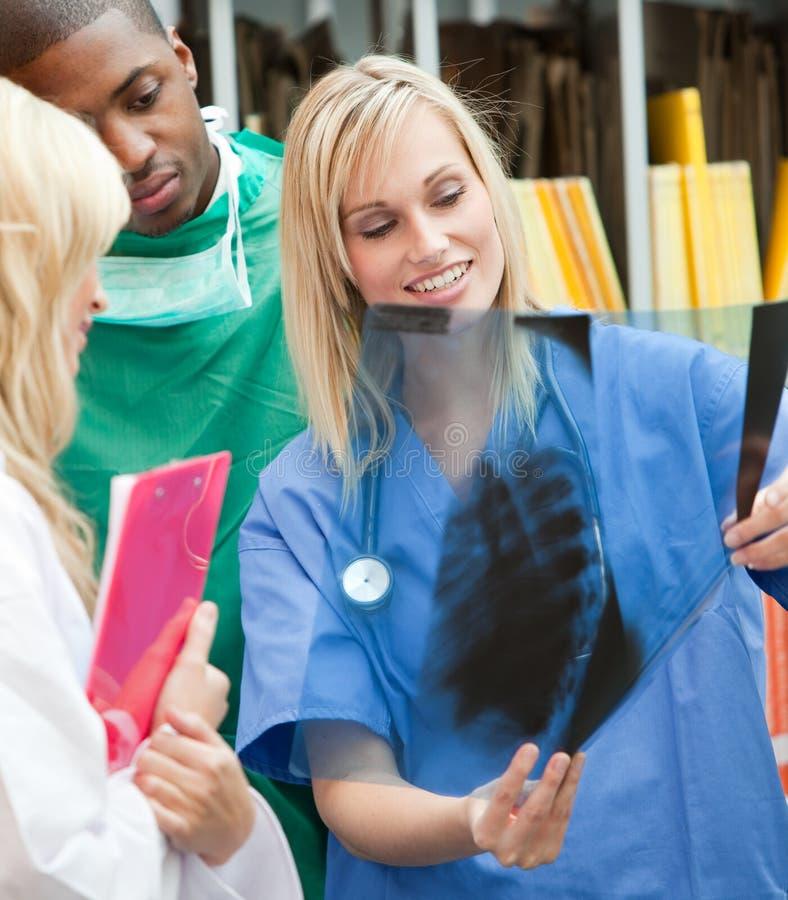 Drie artsen die een röntgenstraal onderzoeken stock foto
