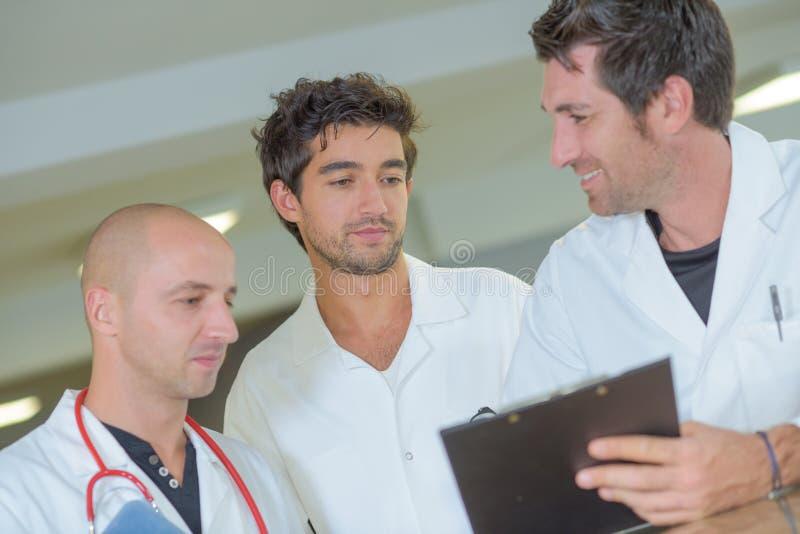 Drie artsen die klembord bekijken stock afbeeldingen