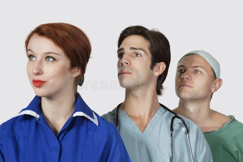 Drie artsen die weg tegen grijze achtergrond kijken stock afbeeldingen