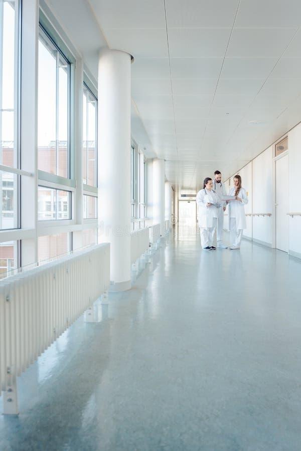 Drie artsen op het ziekenhuisgang die korte vergadering hebben stock foto