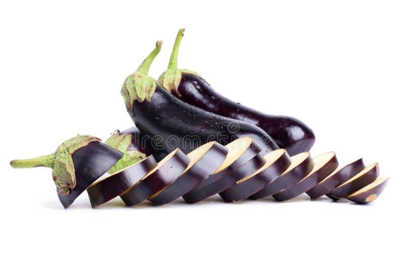 Drie aubergines, wordt één aubergine gesneden in de dalingen van het ringenwater op witte dicht omhoog geïsoleerde achtergrond royalty-vrije stock afbeelding