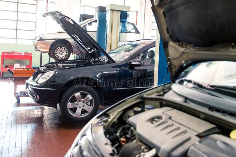 Drie auto's in een reparatiewerkplaats royalty-vrije stock fotografie