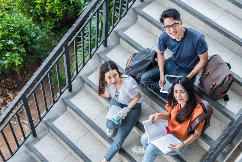 Drie Aziatische jonge campusstudenten genieten tutoring en lezings van boeken samen bij bibliotheektrede Vriendschap en Onderwijs royalty-vrije stock foto