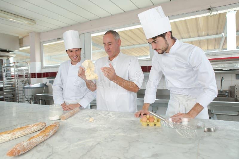 Drie bakkers die in bakkerij vers deeg kneden stock fotografie