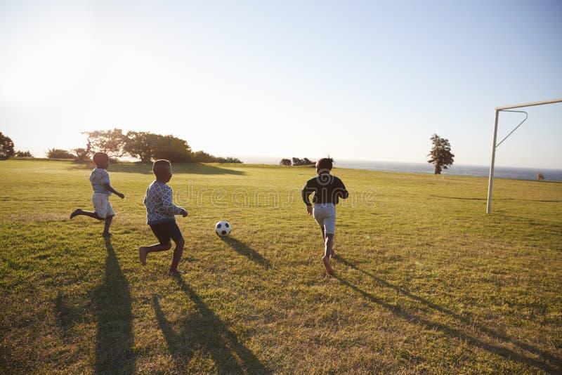 Drie basisschooljonge geitjes die voetbal op een gebied spelen stock foto's