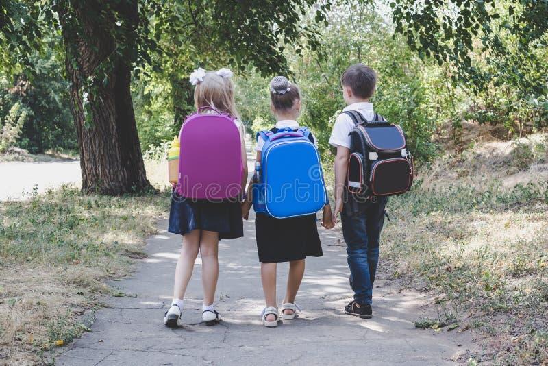 Drie basisschoolstudenten met rugzakken royalty-vrije stock afbeeldingen